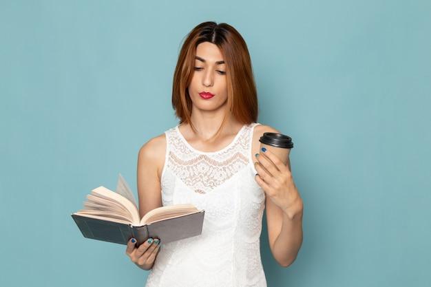 Femme en robe blanche tenant une tasse de café et lisant un livre