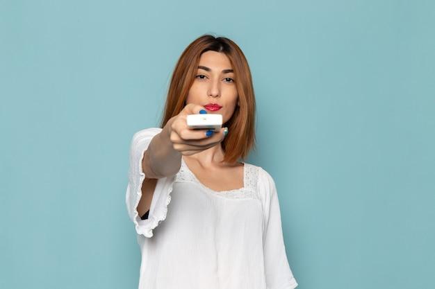 Femme en robe blanche tenant la télécommande