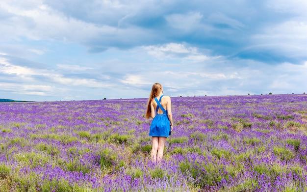 Femme en robe bleue sur champ de lavande par temps nuageux.