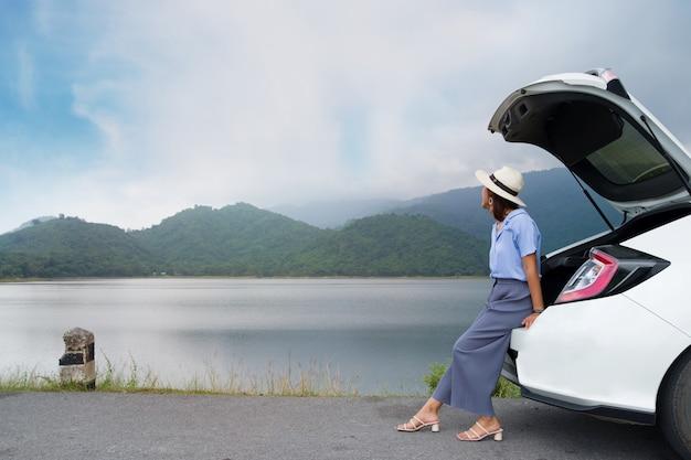 Femme en robe bleue, coiffée d'un chapeau blanc, assise dans le coffre d'une voiture, regardant une montagne avec une rivière