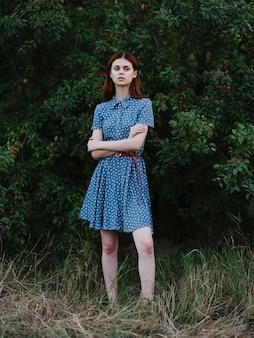 Femme en robe bleue feuilles vertes nature air frais