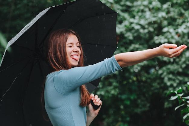 Femme en robe bleue avec parapluie sous la pluie