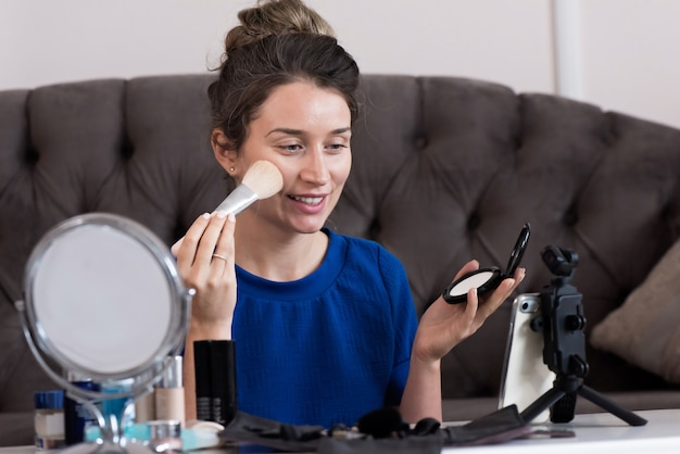 Femme en robe bleue présentant un vlog de maquillage