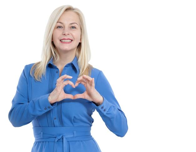 Femme en robe bleue regarde la caméra et montre un geste je t'aime isolé sur blanc.