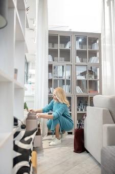 Femme en robe bleue en tricot s'accroupit devant une armoire basse, fermant les tiroirs, souriant de contentement.