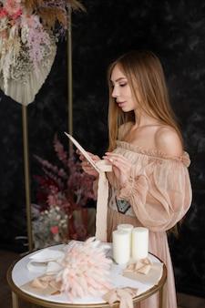 Une femme en robe bohème lit une lettre près de la table