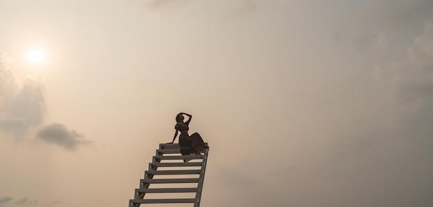 Femme en robe brune assise sur l'escalier, moment du coucher du soleil.