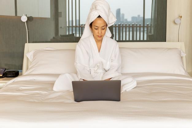 Femme en robe de chambre et serviette sur sa tête est assise dans la chambre sur le lit travaillant sur ordinateur portable.