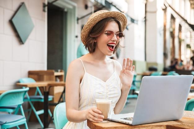 Femme en robe et chapeau de paille parlant par appel vidéo