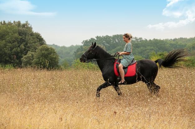 Femme en robe avec un cheval noir dans la nature