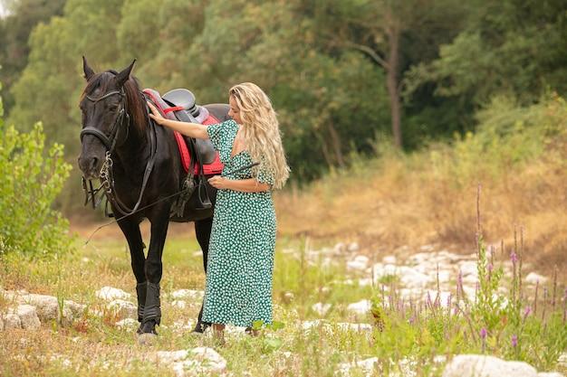 Femme en robe avec un cheval noir
