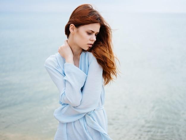 Femme en robe cheveux roux plage océan loisirs air frais