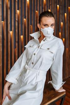 Une femme en robe de combinaison blanche avec un masque antiviral sur son visage. modèle assis sur une chaise