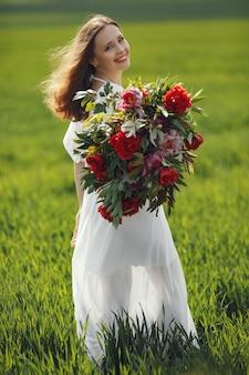 Femme en robe élégante debout dans un champ d'été