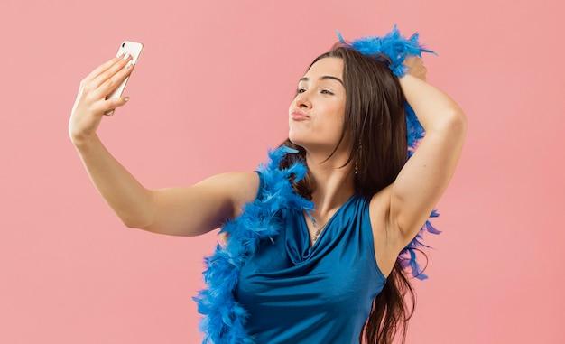 Femme en robe élégante portant des lunettes de soleil à la fête en prenant selfie