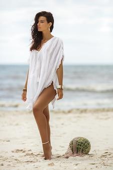 Femme en robe d'été blanche avec pastèque sur la plage