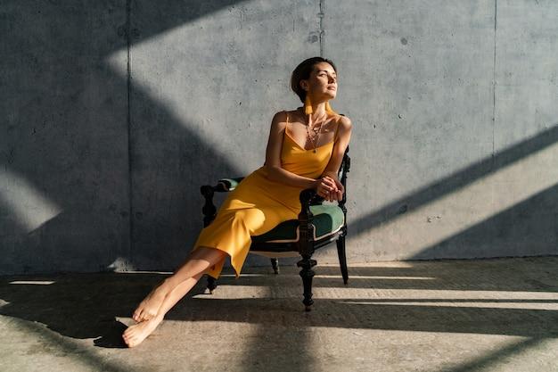 Femme en robe d'été jaune avec une coiffure courte dans la chambre intérieure mur de béton posant