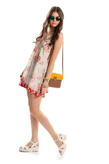 Femme en robe fleurie légère. lunettes de soleil et sac vert foncé. sandales compensées élégantes. le modèle porte des vêtements d'été à la mode.