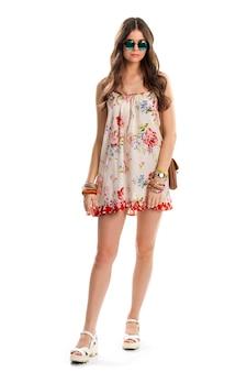 Femme en robe fleurie sans manches. lunettes de soleil et montre vert foncé. look tendance pour l'été. imprimé fleur rouge et bleu.