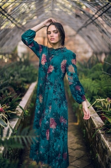 Femme en robe à fleurs bleue, regardant la caméra