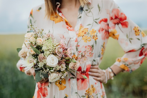Femme en robe à fleurs tenant un bouquet de fleurs