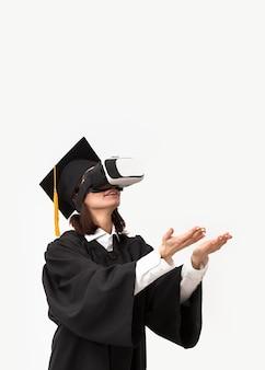 Femme avec robe de graduation et casquette portant un casque de réalité virtuelle