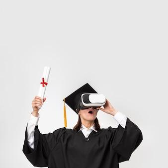 Femme Avec Robe De Graduation Et Casquette Portant Un Casque De Réalité Virtuelle Photo gratuit