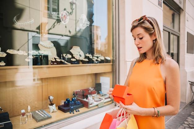 Femme en robe jaune achetée des bijoux