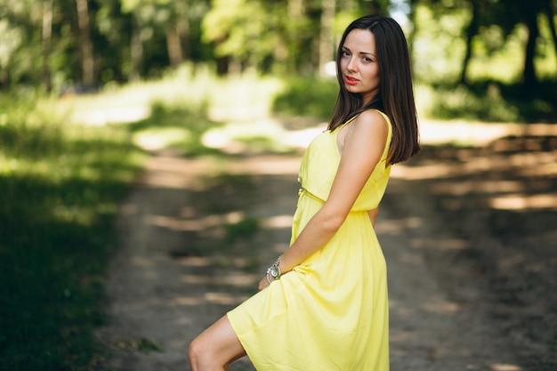 Femme en robe jaune dans le parc