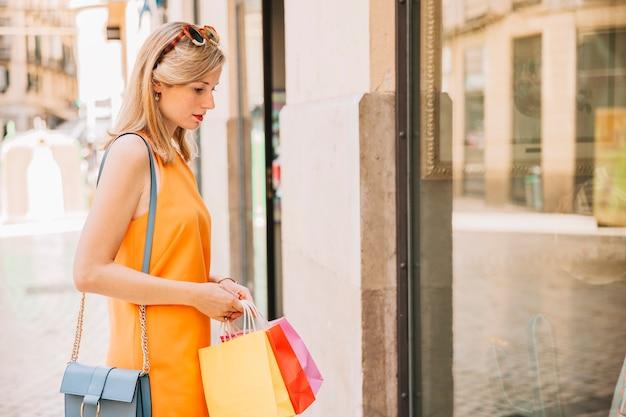 Femme en robe jaune devant un magasin