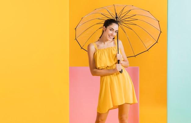 Femme en robe jaune avec un parapluie
