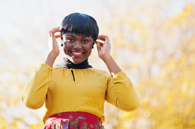 Femme en robe jaune et rouge au parc automne automne doré