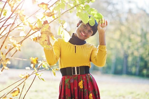 Femme en robe jaune et rouge au parc automne automne