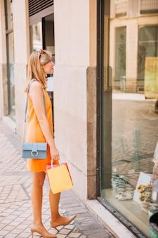 Femme en robe jaune avec des sacs à provisions