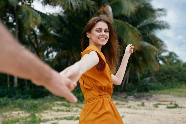Une femme avec une robe jaune se promène le long de l'océan le long du sable avec des palmiers