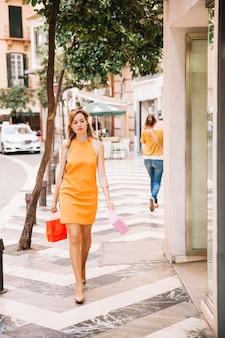 Femme en robe jaune shopping