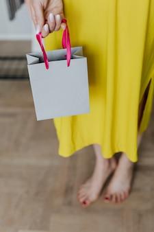 Femme en robe jaune tenant un sac en papier gris