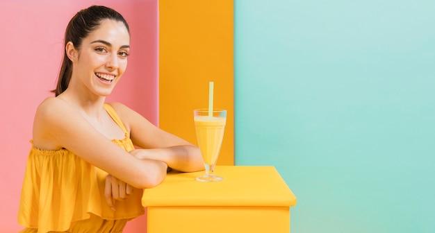 Femme en robe jaune avec un verre de jus