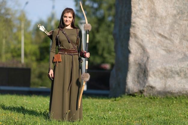 Femme en robe longue tenant un arc et une flèche