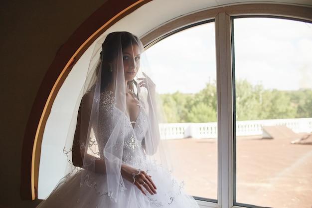 Femme en robe de mariée debout à la fenêtre. mariée en attente de la cérémonie de mariage