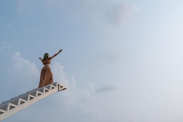 Femme en robe marron, les mains se levant en montant l'escalier. la liberté fait du bien.