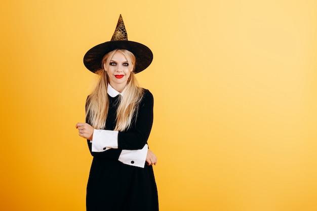 Femme en robe de mascarade et chapeau posant contre le jaune.