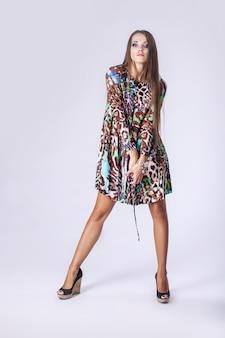 Femme en robe à la mode en pleine longueur en studio sur mur léger
