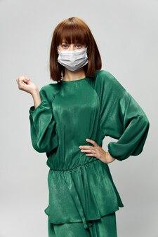 Femme en robe de mode posant dans un masque médical virus covid-19