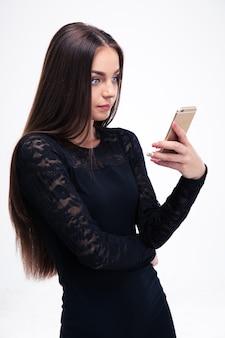 Femme en robe noire à l'aide de smartphone