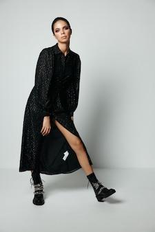 Femme en robe noire bottes noires mode jambes nues. photo de haute qualité