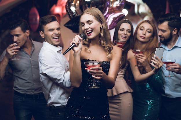 Une femme en robe noire chante des chansons avec ses amis.