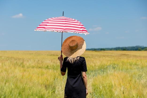 Femme en robe noire et chapeau avec parapluie rouge rester dans le champ de blé