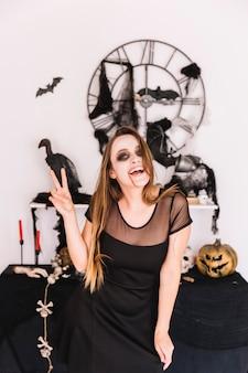 Femme en robe noire devant la composition d'halloween souriant et montrant la paix