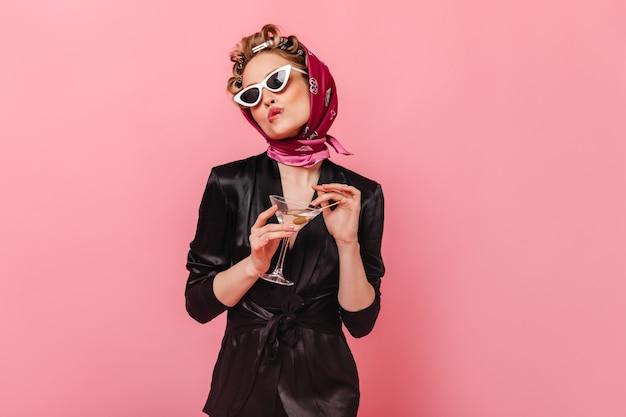 Femme en robe noire et écharpe se mord la lèvre et pose avec martini sur mur rose